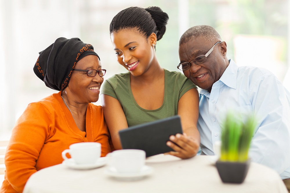 Woman teaching her grandparents how to use facebook