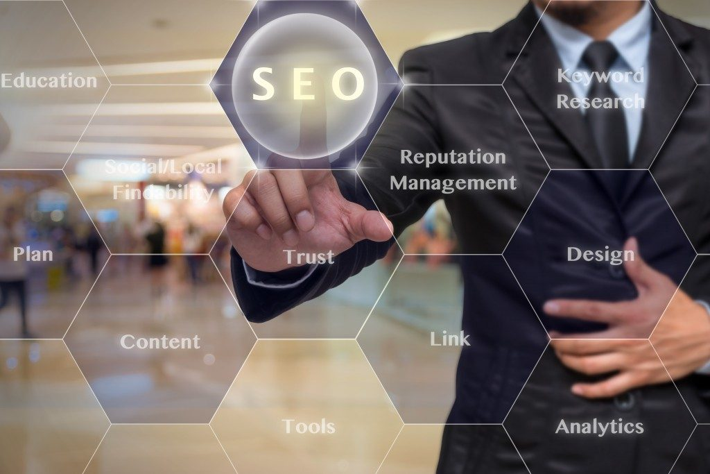 Businessman pointing at holographic SEO words