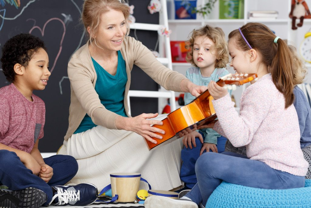Teacher handing little girl the guitar