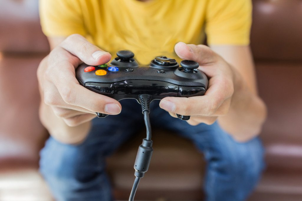 An Asian young man holding game controller playing video games