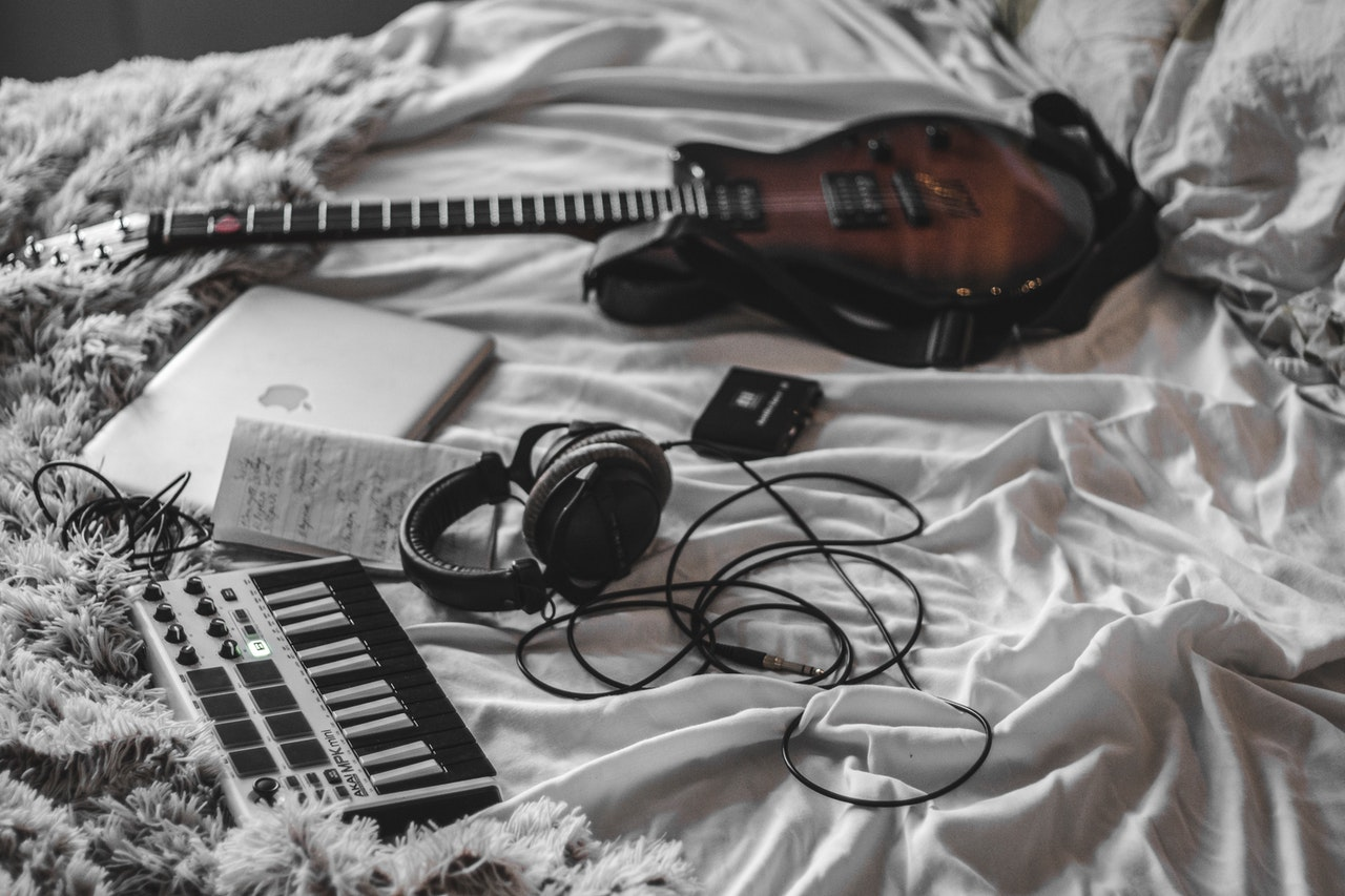 midi keyboard and electric guitar on the bed