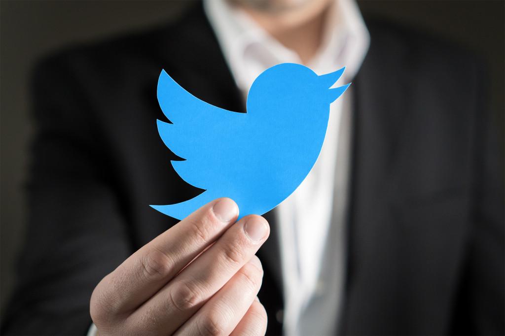 man holding twitter logo